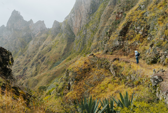Traveler with camera in front of the monumental mountain ridge and ravine on the cobbled path to Xo - Stock Photo - Images