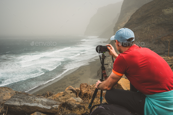 Tourist making photograph of cliff coastline with ocean waves from Cruzinha to Ponta do Sol. Huge - Stock Photo - Images
