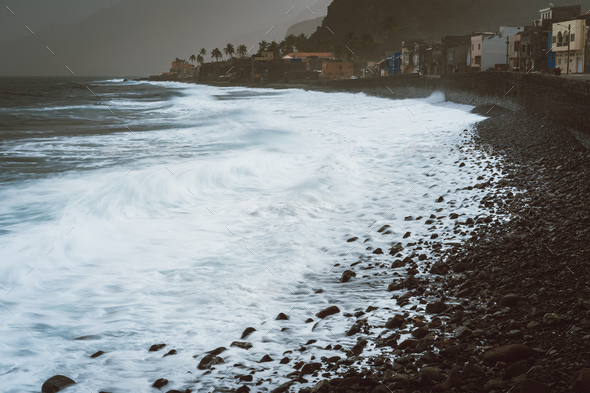 Rough ocean waves with blowing spray rolling onto the rocky volcanic shore. Ribeira Grande Village - Stock Photo - Images