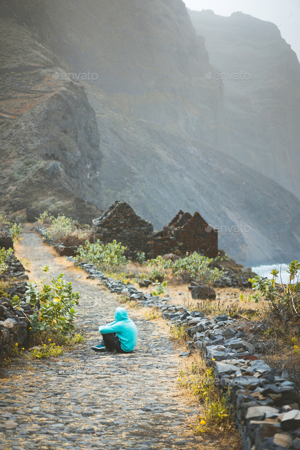 Traveler in hoodie sitting in Aranhas valley in front of amazing rocks with old path from Cruzinha - Stock Photo - Images