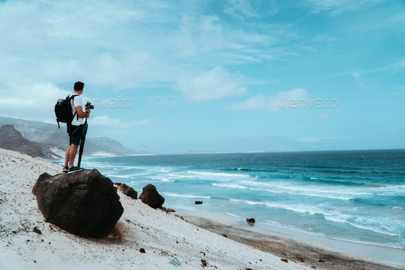 Traveler with camera staying on the black volcanic boulder and admiring unusual barren landscape of - Stock Photo - Images