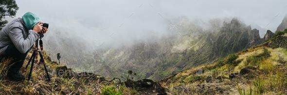 Panoramic shot of traveler making photo of amazing steep mountainous terrain with lush canyon valley - Stock Photo - Images