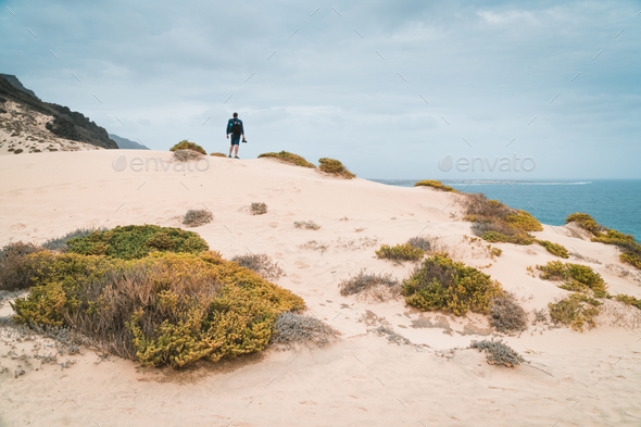 Ttraveler and photographer on the top of snow-white dune landscape on the Atlantic coastline. Sao - Stock Photo - Images