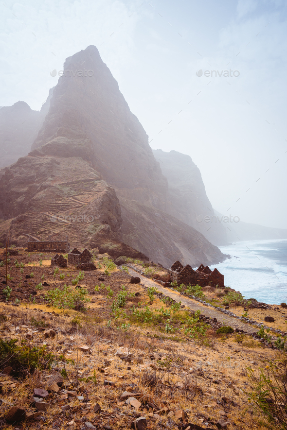 Aranhas mountain peak in the valley with house ruins and stony hiking path going up the mountain - Stock Photo - Images