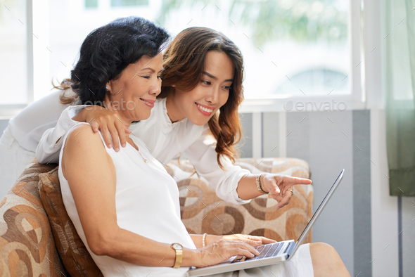 Mother and daughter with laptop - Stock Photo - Images