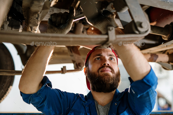 Bearded worker of technical service concentrating on examination of car engine - Stock Photo - Images