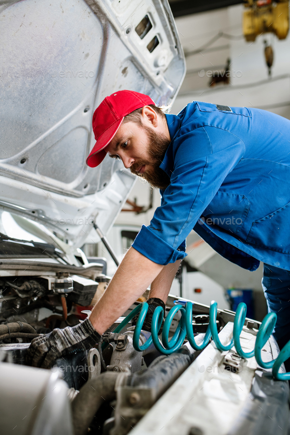 Serious young bearded engineer of maintenance service bending over engine - Stock Photo - Images