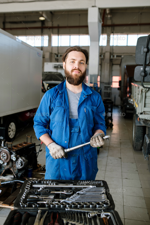 Young bearded master of technical repair standing inside workshop - Stock Photo - Images