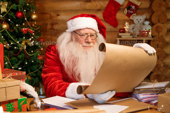 Serious Santa in white gloves, eyeglasses and costume reading Christmas wishes - Stock Photo - Images