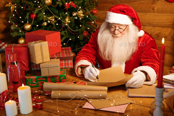 Santa with long white beard writing down answers for Christmas letters - Stock Photo - Images