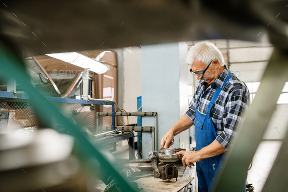 Aged grey-haired master of repair service fixing engine parts with wrench - Stock Photo - Images
