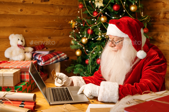 Contemporary Santa in costume sitting by desk in front of laptop at home - Stock Photo - Images