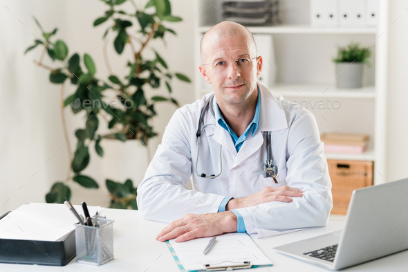 Young confident clinician in whitecoat sitting by desk in front of laptop - Stock Photo - Images