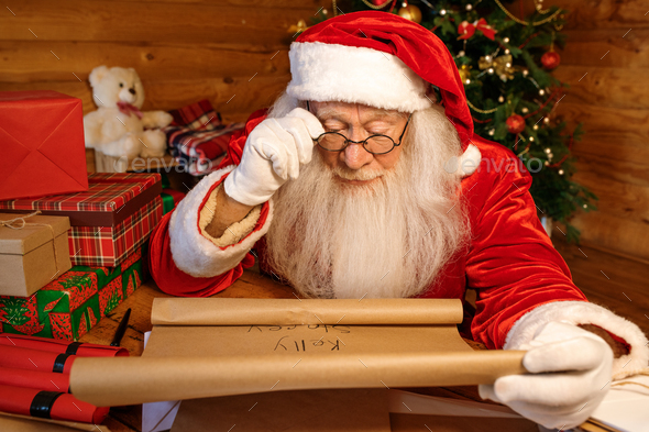 Santa reading paper with names of kids who waiting for Christmas presents - Stock Photo - Images