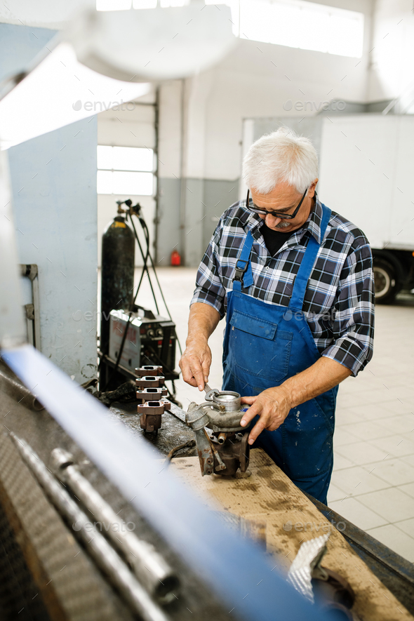 Senior professional technician in overalls and shirt working with wrench - Stock Photo - Images