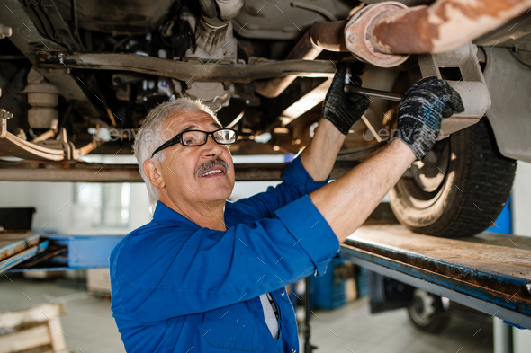 Senior technician of repair service with worktool fixing details of car - Stock Photo - Images