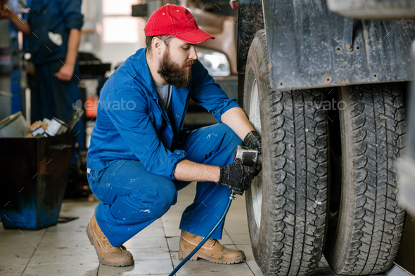 Serious young technician in workwear doing repair work with electric drill - Stock Photo - Images