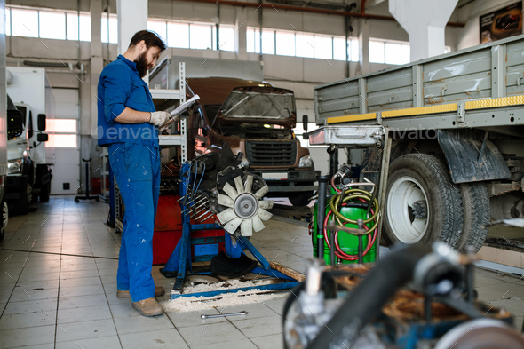 Young serious worker of automobile repair service reading instructions - Stock Photo - Images