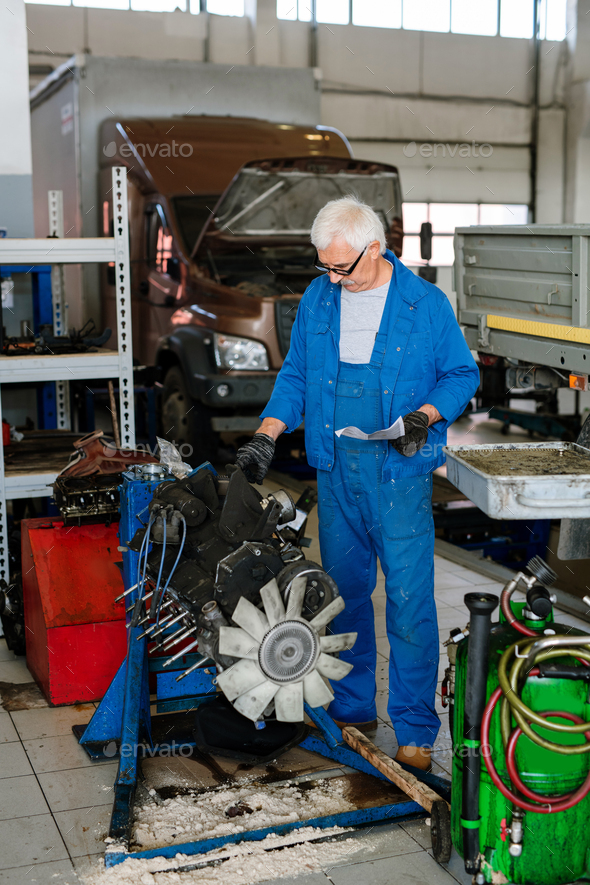 Mature grey-haired master of technical repair service workshop touching engine - Stock Photo - Images