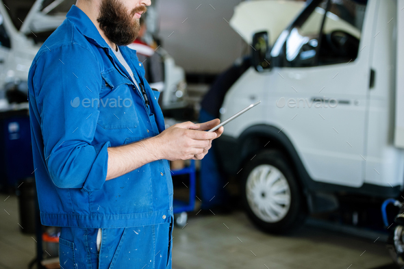 Young contemporary worker in blue uniform surfing for online orders in workshop - Stock Photo - Images