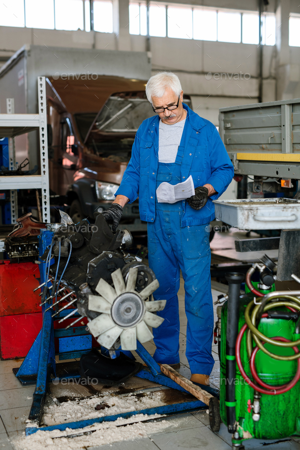 Senior master of car service of maintenance reading paper with instructions - Stock Photo - Images