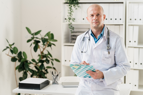 Serious and confident doctor with clipboard and pen making prescriptions - Stock Photo - Images