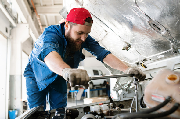 Young technician in workwear bending over engine of car or lorry - Stock Photo - Images