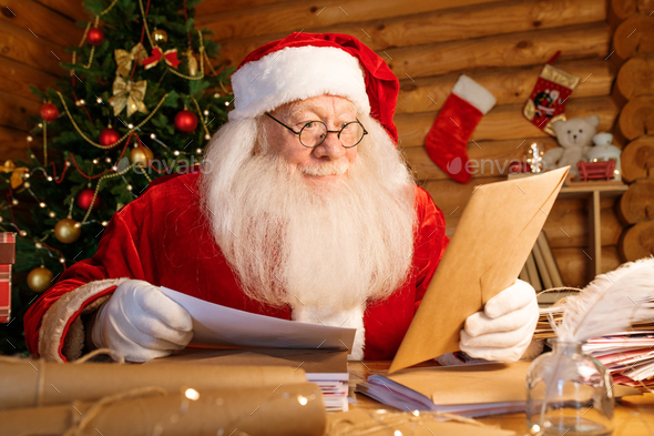 Santa with white beard sitting by table while looking at envelope in his hand - Stock Photo - Images