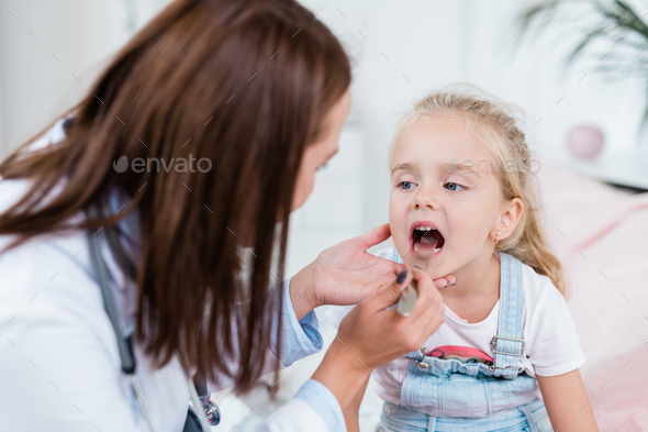 Sick child opening mouth while looking at doctor examining her sore throat - Stock Photo - Images
