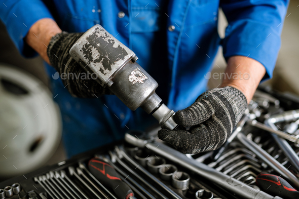 Gloved repairman in workwear putting one of nozzles on metallic drill - Stock Photo - Images