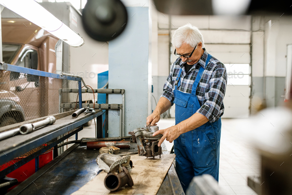 Mature professional repairman of car maintenance service standing by workbench - Stock Photo - Images
