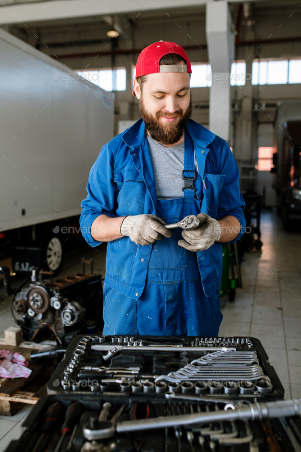 Contemporary young worker of car repair service standing by motor of automobile - Stock Photo - Images