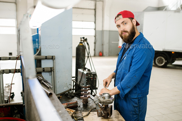 Young bearded repairman using wrench or other handtool to fix parts of engine - Stock Photo - Images