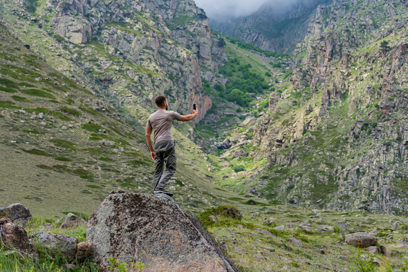 Male hiker takes photo of beautiful mountains while standing on rock - Stock Photo - Images