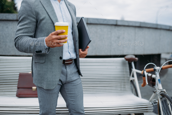 Businessman with cycle drinks coffee on the bench - Stock Photo - Images