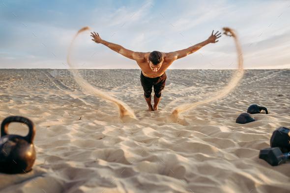Push-up exercises in desert, flying sand effect - Stock Photo - Images
