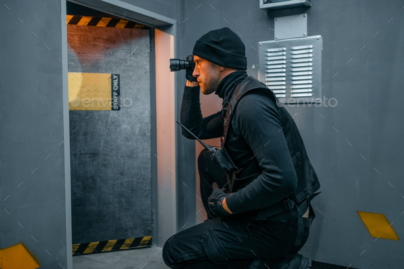 Male robber in black uniform holds gun and lantern - Stock Photo - Images