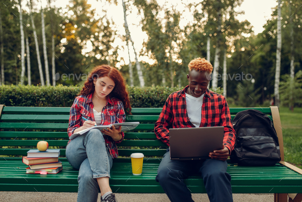 Two students sitting on the bench in summer park - Stock Photo - Images