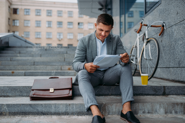 Businessman with bike having lunch at the office - Stock Photo - Images