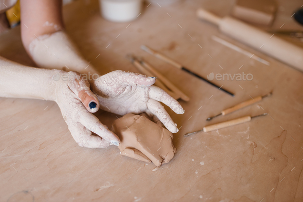 Female potter hands covered with dried clay - Stock Photo - Images