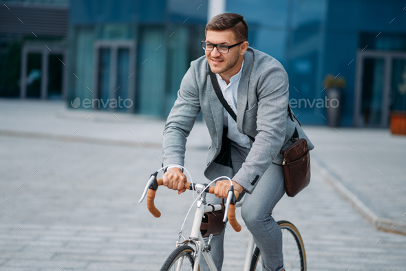 Businessman poses on bicycle at office building - Stock Photo - Images