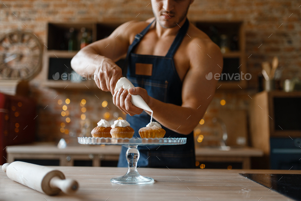 Nude man in apron cooking dessert on the kitchen - Stock Photo - Images