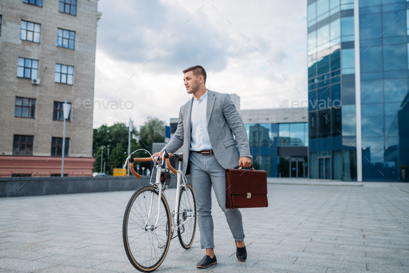 Businessman with briefcase and bicycle in downtown - Stock Photo - Images