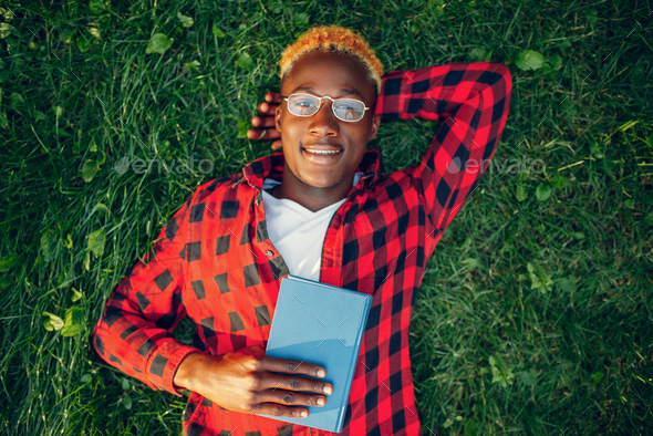Black student in glasses reading book on the grass - Stock Photo - Images