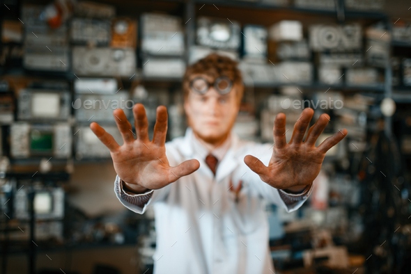 Strange scientist showing scorched hands in lab - Stock Photo - Images