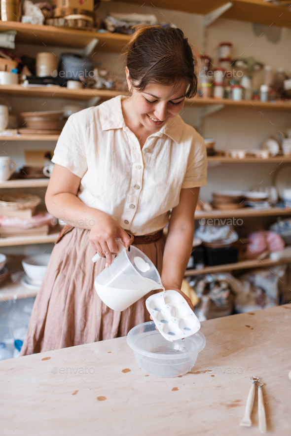Female potter washes a foarm, pottery workshop - Stock Photo - Images