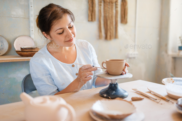 Female potter skins pot with a spatula, pottery - Stock Photo - Images