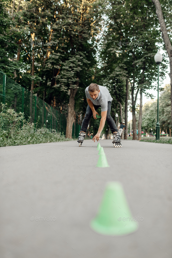 Roller skating, male skater puts the cones in park - Stock Photo - Images
