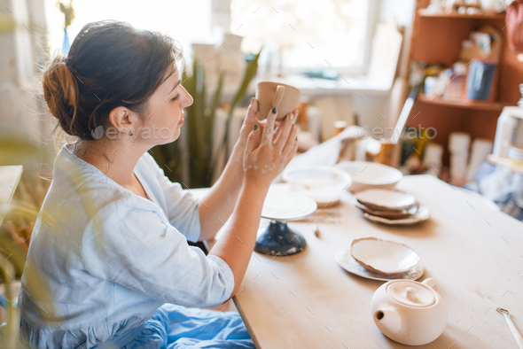 Female potter skins pot with her fingers - Stock Photo - Images