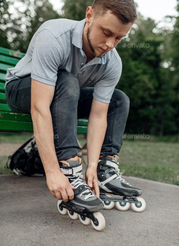 Roller skating, male skater puts on skates in park - Stock Photo - Images